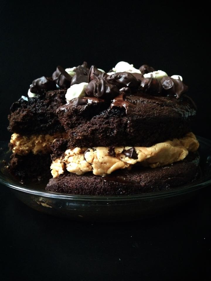 Dark Chocolate Cake with Peanut Butter Fudge Chunk Cookie Dough Frosting, Salted Caramel Glaze, and Triple Chocolate-Covered Pretzel Bites | Whisk and Shout